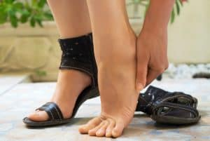 Woman rubbing her sore tired feet.