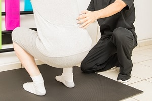Young physical therapist assisting mature man doing squats in clinic